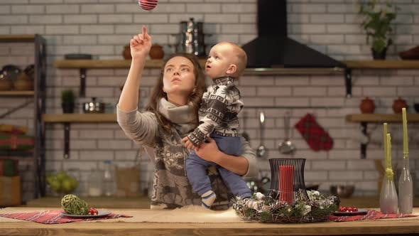 Thumbnail for Pretty Young Woman Lifts Up the Baby in Her Arms Standing in Modern Kitchen Showing To Son Bright