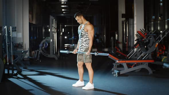 Cover Image for Handsome Sportsman Trains Hands Shoulders with Barbell Weight