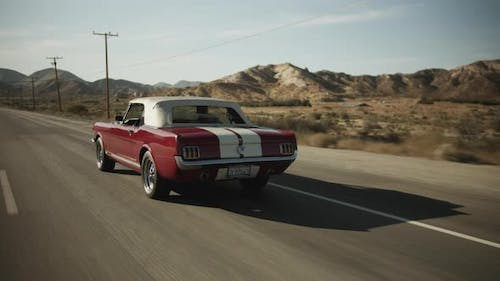 Old Mustang Car Driving on Scenic Highway in California Surrounded By Desert, Tracking Follow Shot