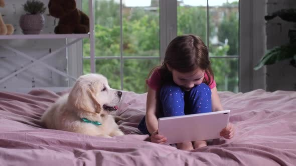 Thumbnail for Girl Watching Funny Cartoon with Pet Dog Indoors