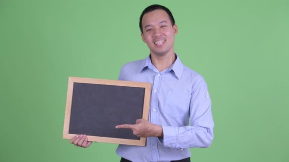Cover Image for Happy Asian Businessman Holding Blackboard and Giving Thumbs Up