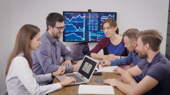 Cover Image for Group of Young Financial Specialists Is Sitting in Meeting Room with Display with Schedules on Wall