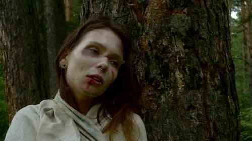 Nahaufnahme einer gewaltsam geschlagenen Frau, die im Wald mit einem Schlagen im Gesicht steht