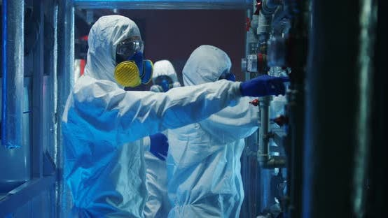 Scientists in Hazmat Suits Checking Equipment