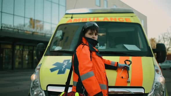 Proud Female Paramedic Posing at Ambulance Vehicle Near Hospital