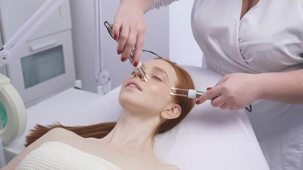 Microcurrent Treatment of the Face with Hyaluronic Acid for a Young Woman in a Cosmetology Clinic