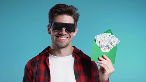 Cover Image for Happy European Man in Glowing with Dollar Signs Glasses Showing Money in Envelope - U.S. Currency