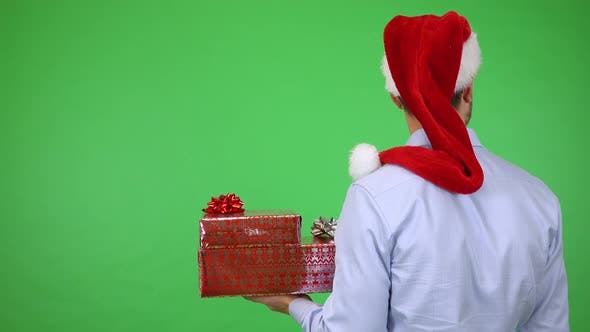 Thumbnail for A Man in a Christmas Hat Holds Presents Back To the Camera and Looks Around - Green Screen Studio