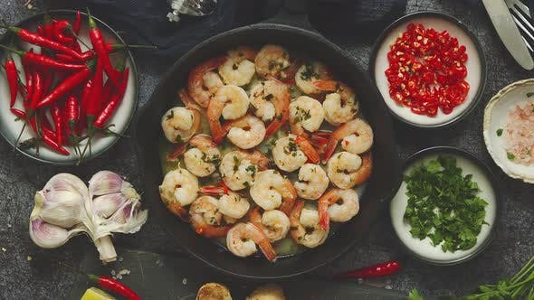 Fried Baby Shrimps Served on Iron Pan and Fresh Herbs and Ingredients. Top View, Flat Lay