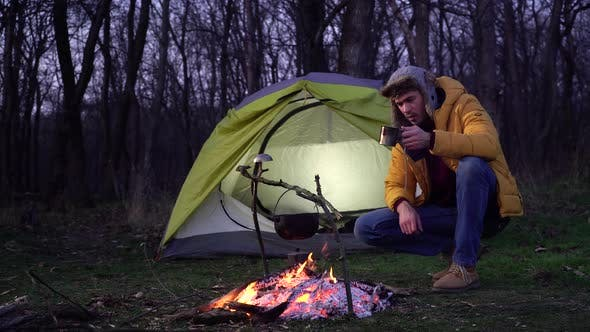 Thumbnail for A Man Near a Campfire and a Tent in the Forest