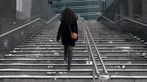 A Curlyhaired Woman in a Fur Coat Climbs the Stairs in the City Enjoying a Beautiful Day