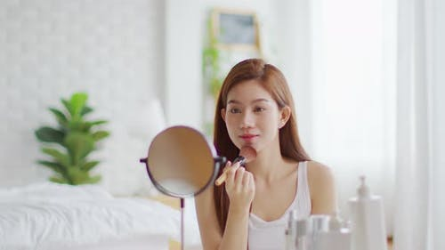 Happy Asian young woman smile and looking in mirror doing skin care applying make up brush on cheek