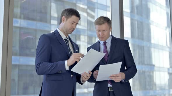 Two Middle Aged Businessmen Reading Documents Against Boardroom Office Window