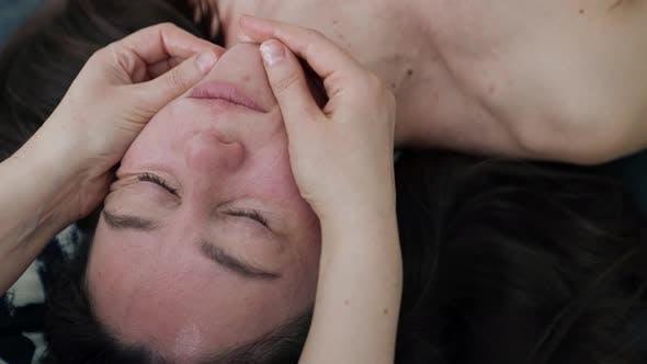 Ästhetikerin macht Gesichtsmassage für Patientin mittleren Alters im Schönheitssalon