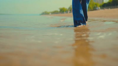 Waves Wet Jeans and Bare Feet of a Girl