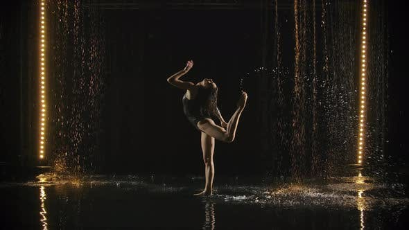 Fragile Gymnast Performs Acrobatic Movements on the Surface of the Water in Slow Motion. Woman's