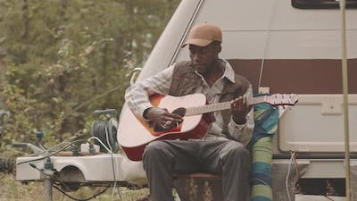 African-American Man Playing Guitar in Forest