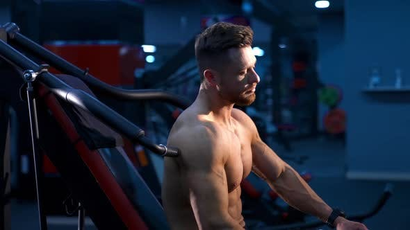 Brutal strong athletic man pumping up muscles. Doing workout on sport equipment