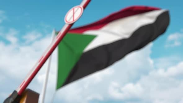 Geschlossenes Boom-Tor mit STOP CORONAVIRUS-Zeichen an der Flagge des Sudan