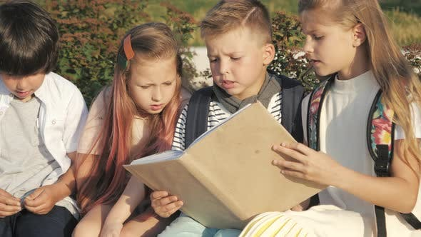 Thumbnail for Pupils Looking Through Encyclopaedia Outdoors.