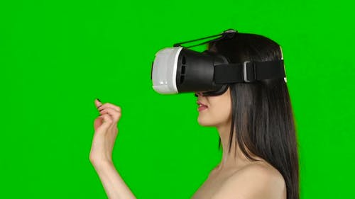 Virtual Reality Game. Girl with Surprise and Pleasure Uses Head-mounted Display. Green Screen. Close