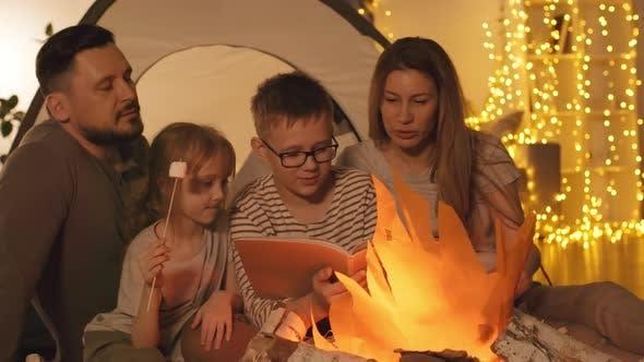 Thumbnail for Family Reading Book near Artificial Bonfire