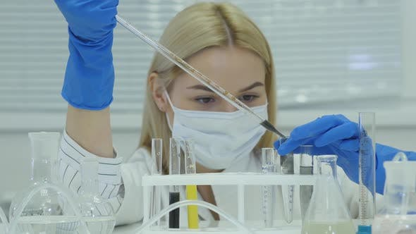 Thumbnail for Chemical Research Scientist Working In The Lab. Scientist In Protective Workwear Pour Liquid In Tube