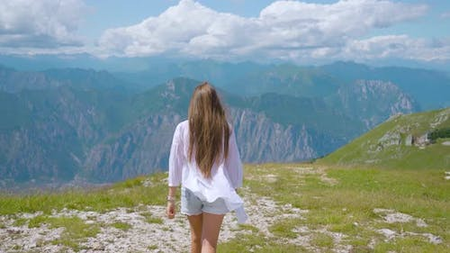 Young Girl Walks on the Alps Mountains in Summer