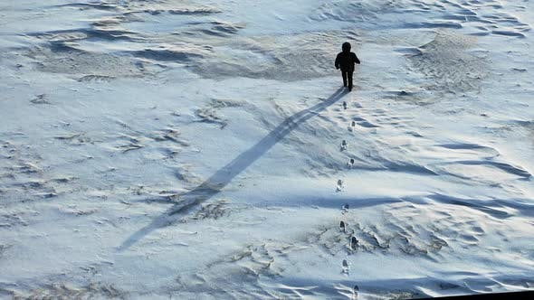 Thumbnail for Lonely Human Walking Through a Snowy Desert. View From Drone