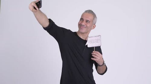Happy Handsome Persian Man Taking Selfie with Paper Sign