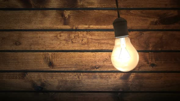 Cover Image for Swinging Incandescent Bulb in Timber-house Darkened Room