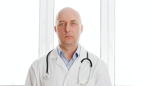 Thumbnail for Male Doctor in Medical Gown with Phonendoscope Swiping Virtual Screen in White Window Background