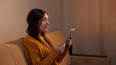 Concentrated Brunette in Yellow Sweater Reads Ebook on Sofa