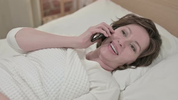 Thumbnail for Attractive Old Woman Talking on Smartphone in Bed