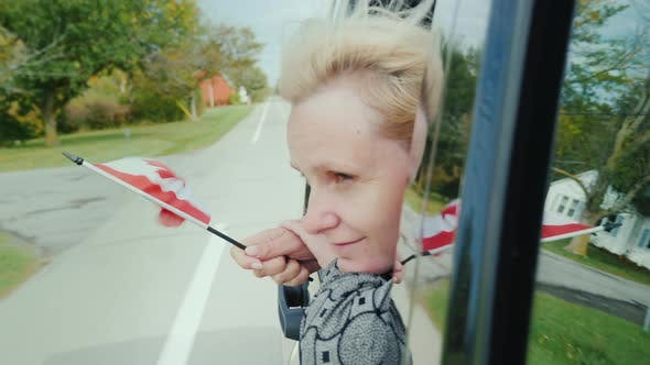 Cover Image for A Woman Is Looking Out of the Car Window, Holding a Canadian Flag in Her Hand
