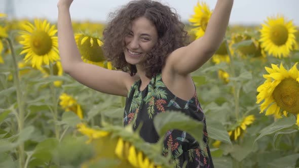Thumbnail for Portrait of Beautiful Curly Girl Dancing and Laughing Looking at the Camera in the Sunflower Field