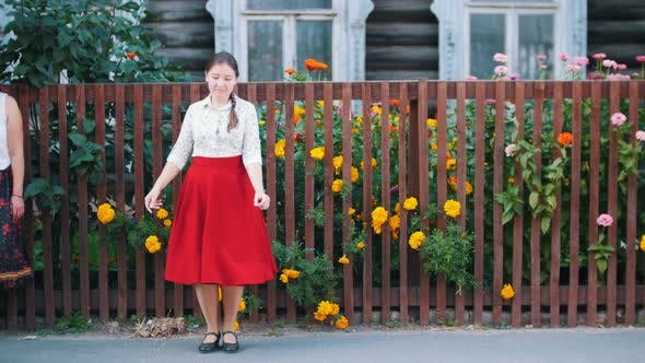Thumbnail for A Young Woman in Long Red Skirt Dancing By the Fence on the Street
