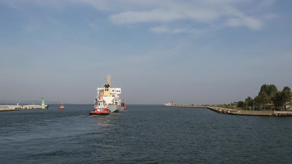 Thumbnail for Container Cargo Ship with Tugboat or Auxiliary Boat goes out from port to the sea at summer day