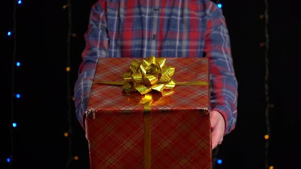 Thumbnail for Boy with a Gift Box on Black Background. Gift Box with Ribbon for Happy New Year, Merry Christmas