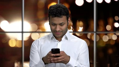 Handsome Guy Typing Message on His Smartphone.