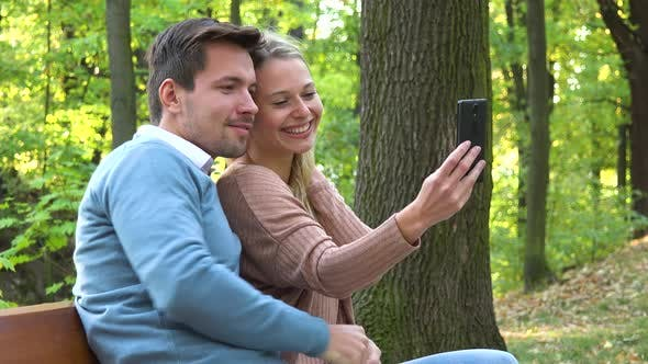 Thumbnail for A Young Attractive Couple Take Selfies with a Smartphone in a Park on a Sunny Day