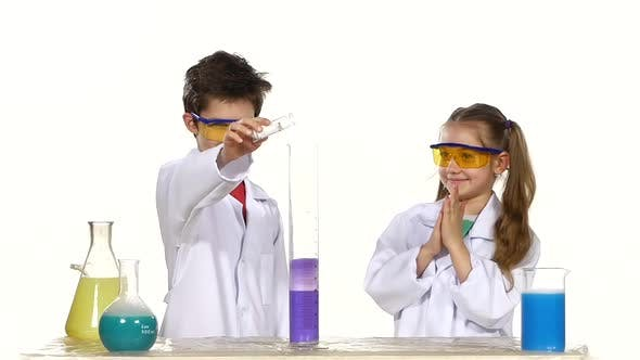 Two Cute Chemist Children Making Interesting and Successful Experiments Isolated on White Background