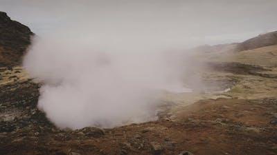 Zooming Shot of a Mountain Range Releasing Vapor Underneath