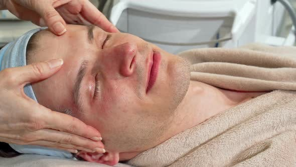 Thumbnail for Handsome Man Smiling To the Camera, Receiving Face Massage at Spa Center