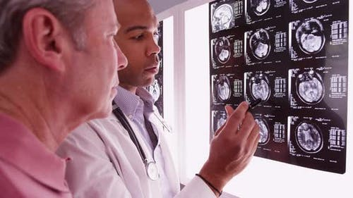 Mid aged male patient looking at xrays with radiologist