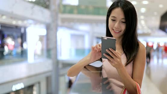 Cover Image for Woman use of mobile phone in shopping mall