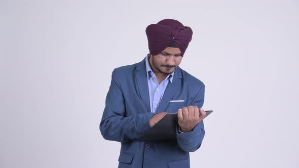 Thumbnail for Stressed Indian Sikh Businessman Showing Clipboard and Giving Thumbs Down