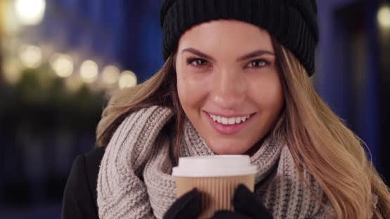 Thumbnail for Cheerful female in cozy hat and scarf enjoying hot coffee outside