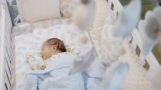 Cute Baby Sleeping in the Crib with Children's Soft Toys