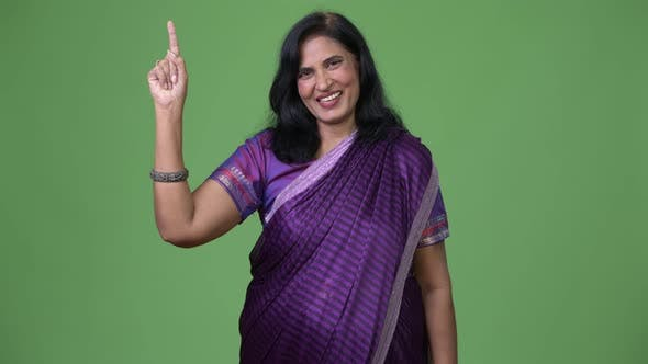 Mature Happy Beautiful Indian Woman Pointing Up While Wearing Sari Traditional Clothes